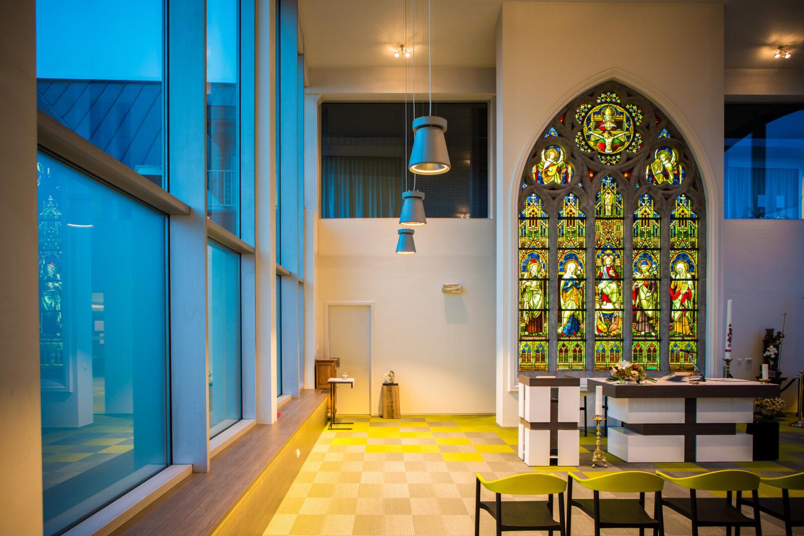 Monumentaal brandglasraam uit kapel Zusters Groene Briel (Gent), geïntegreerd in kapel WZC Westervier (Brugge) als tussenwand, verlicht met LED-sheets – © Wove